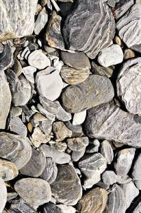 Stock photo of the schist rocks on the banks of the river at Fantail Falls in Mt Aspiring National Park, Haast Highway near Haast Pass, West Coast, South Island, New Zealand.