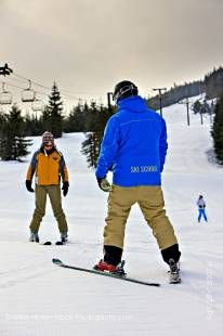 Stock photo of a ski instructor with a student on the beginner's slope of Whistler Mountain, Whistler Blackcomb, Whistler, British Columbia, Canada.