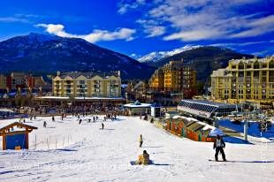 Stock photo of skiers and snowboarders at the base of Whistler Mountain and the Excalibur Gondola Lift, Whistler Village, British Columbia, Canada.