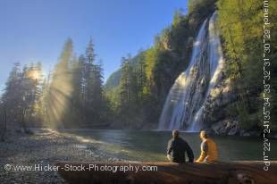 Stock photo of a man and a woman sitting on a log enjoying the scenic view of Virgin Falls near Tofino on Vancouver Island with sun rays filtering through the rain forest.