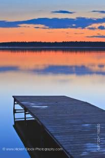 Stock photo of a wooden wharf extending onto Lake Audy looking out to the golden reflection of the magnificent sunset at Lake Audy, Riding Mountain National Park, Manitoba, Canada.