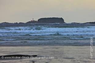 Stock photo of the stormy waves of the Pacific Ocean at the beach in Cox Bay near Tofino with the Lennard Island Lighthouse in the background, a transition area of the Clayoquot Sound UNESCO Biosphere Reserve, West Coast, Vancouver Island, British Columbi
