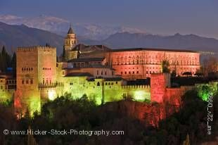 Stock photo of The Alhambra (La Alhambra) a moorish citadel and palace designated a UNESCO World Heritage Site in 1984, backdropped by the snowcapped Sierra Nevada mountain range seen from Mirador de San Nicolas in the Albayzin district at dusk, Granada.
