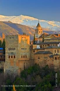 Stock photo of The Alhambra (La Alhambra) a Moorish citadel and palace (designated a UNESCO World Heritage Site in 1984), back dropped by the snow capped Sierra Nevada mountain range seen from Mirador de San Nicolas in the Albayzin district at sunset, Cit