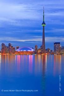 Stock photo of the Toronto city skyline illuminated at dusk, highlighting the CN Tower and Rogers Centre on the waterfront shore of Lake Ontario, Ontario, Canada.