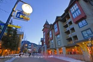 Stock photo of the Town Plaza along the Village Stroll at dusk in Whistler Village, British Columbia, Canada. Above the sky is still blue but at street level the buildings are illuminated as night falls and people walk along the Village Stroll in pictures
