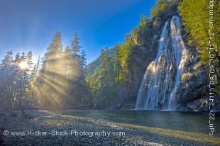 Stock photo of the Virgin Falls plunging 53 metres/174 feet in a fan formation down a rock escarpment along the Tofino Creek with rays of sunlight streaming through the trees, a transition area of the Clayoquot Sound UNESCO Biosphere Reserve, Vancouver Is