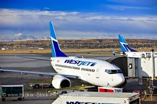 Stock photo of a WestJet Boeing 737-600 aircraft on the apron at the Calgary Airport with the buildings of downtown Calgary in the background, City of Calgary, Alberta, Canada. The sky is striped with bands of thick white clouds and clear blue sections.