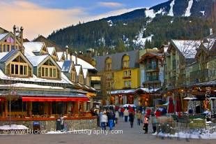 Stock photo of pedestrian activity and shops along the Village Stroll in Whistler Village, British Columbia, Canada. The tall rooftops are mostly snow covered as are the mountains in the background.