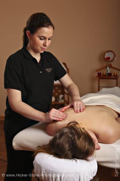 Stock photo of Masseuse giving body massage to female
