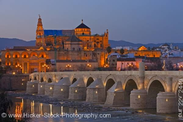 Stock photo of Puente Romano spans Rio Guadalquivir leads to Mezquita during dusk in City of Cordoba