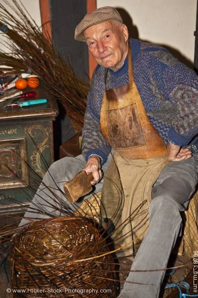Stock photo of Elderly man weaving branches medieval markets castle Ronneburg