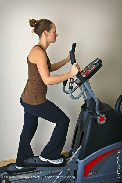 Stock photo of Woman working out elliptical trainer