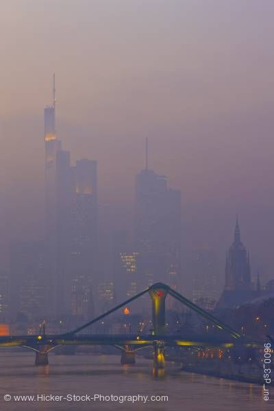 Stock photo of Bridge skyscrapers foggy city of Frankfurt and the Main River at dusk Hessen Germany Europe