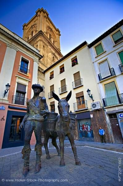 Stock photo of Man and donkey statue Plaza de la Romanilla and bell tower of Cathedral City of Granada