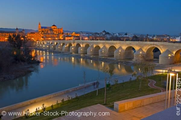 Stock photo of Puente Romano bridge spans Rio Guadalquivir to Mezquita at dusk in City of Cordoba Andalusia