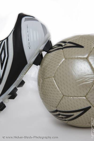 Stock photo of Soccer shoe leaning against a soccer ball