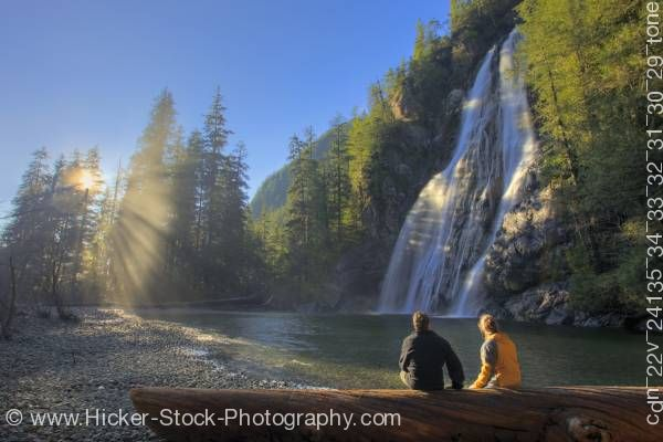 Stock photo of Sun rays and couple Virgin Falls Tofino Creek Vancouver Island British Columbia Canada