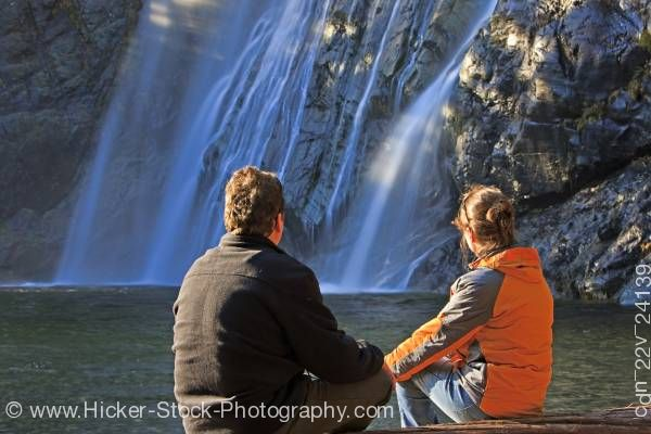 Stock photo of Couple Viewing The Virgin Falls Along Tofino Creek Vancouver Island British Columbia Canada